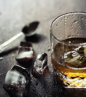 ガラスと氷とウイスキー。木製のテーブルと冷やした強いアルコールとガラスの上の氷の立方体。アメリカンウイスキー、バーボン、カードが入ったテーブル。