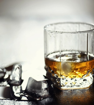 Whiskey with ice with a glass. cubes of ice on a wooden table and a glass with chilled strong alcohol. table with american whiskey, bourbon and cards.