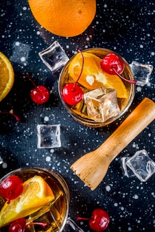 Whiskey with orange and cocktail cherries