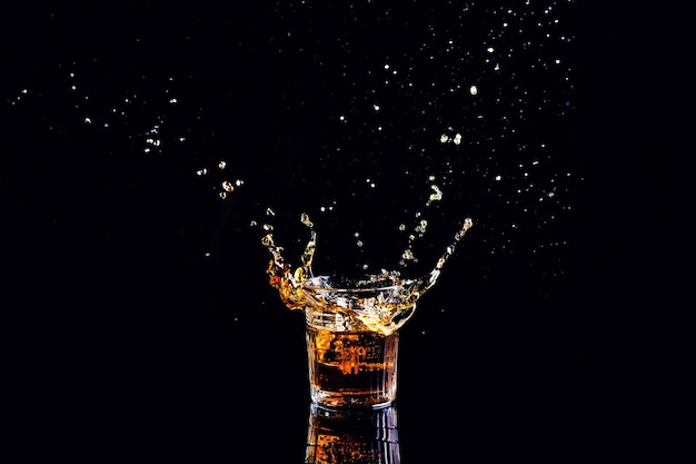 Whiskey with splash on black surface, brandy in a glass