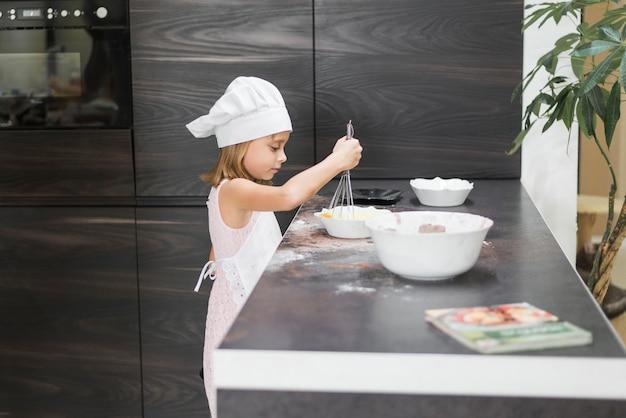 台所のワークトップのボウルに一緒に混合物をwhisking女の子の側面図
