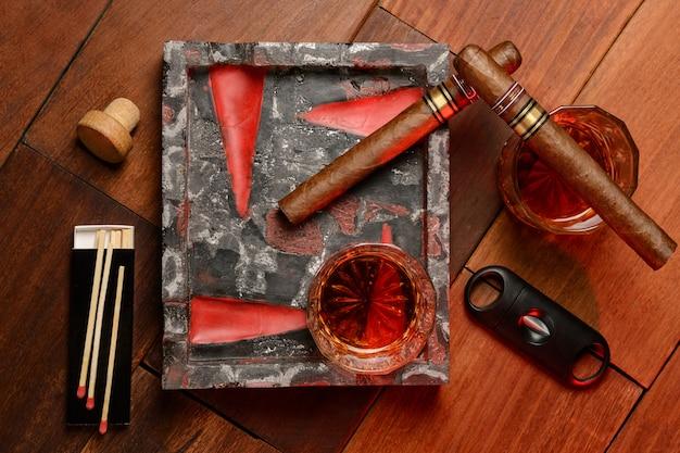 Виски, сигары и пепельница на деревянном столе. вид сверху
