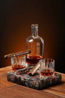 Whisky, cigars and ashtray on the wood table