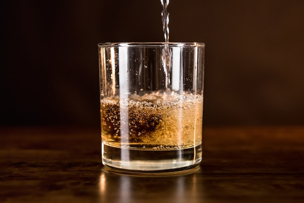 Whisky drink being poured in into the glass on wooden counter bar