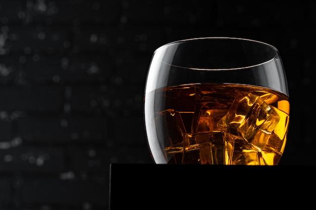 暗い黒グランジ壁にウイスキーグラス