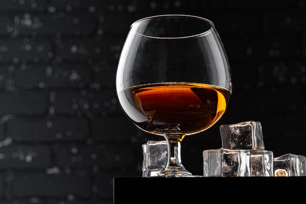 Whisky glass against dark black grunge wall