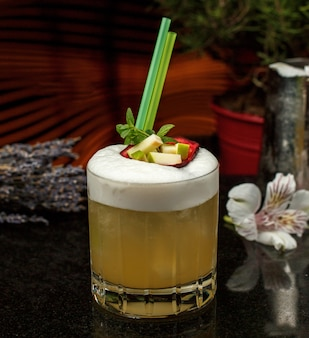 A whisky glass of fresh apple juice garnished with apple pieces and straw