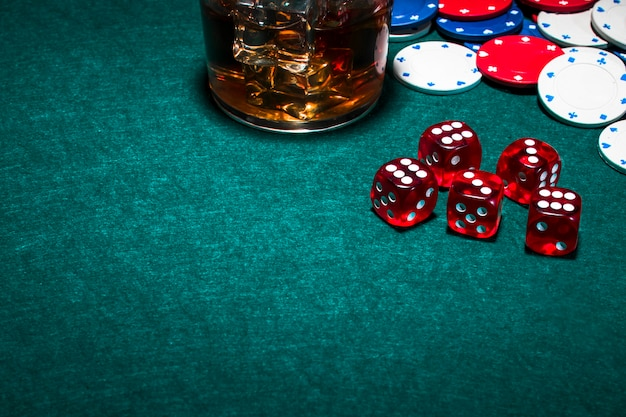Whisky glass with ice cubes over the gambling table