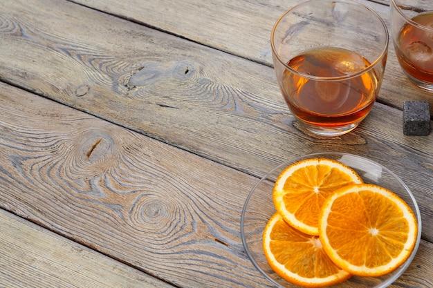 Whisky glass with orange fruit cut on dark wooden