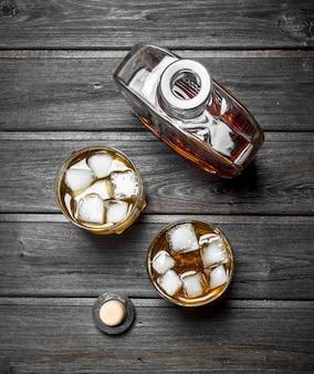 ボトルとグラスのウイスキー。黒い木製のテーブルの上