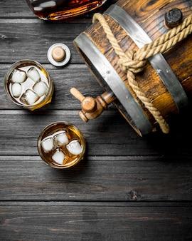 グラスと樽に入ったウイスキー。黒い木製のテーブルの上