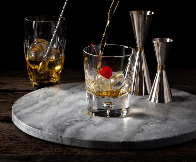 Whisky pouring in glass with cherry and jigger bartender