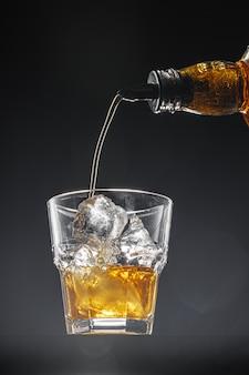 黒の背景にグラスに注ぐウイスキー