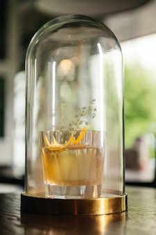 Whisky & smoke. autumn old fashion with orange and thyme. experimental alcoholic cocktail in a flask with smoke