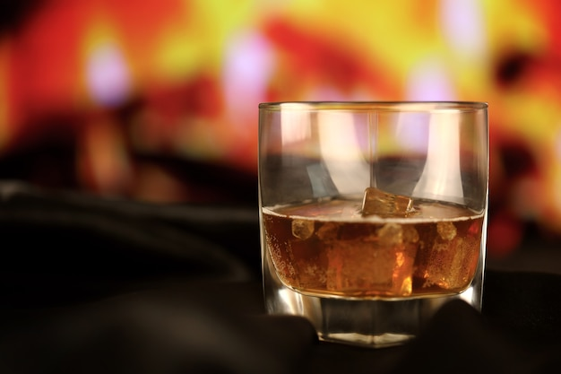 Whisky or whiskey or bourbon with ice on wooden surface on fireplace background