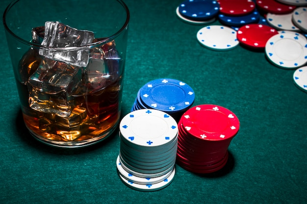 Whisky with ice cubes and casino chips stack on green poker backdrop