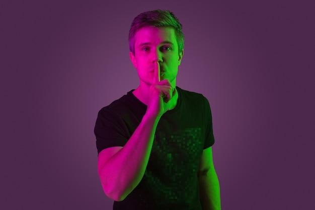 秘密をささやく。コピースペース。ネオンの光の紫色のスタジオの背景に白人男性の肖像画。黒のシャツを着た美しい男性モデル。人間の感情、顔の表情、販売、広告の概念。