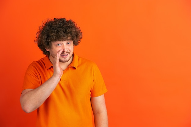 Whispering a secret. caucasian young man's monochrome portrait on orange wall. beautiful male curly model in casual style.