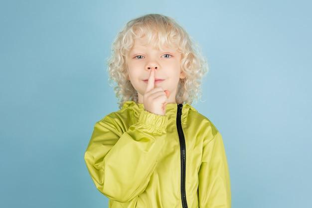 Whispering a secret. portrait of beautiful caucasian little boy isolated on blue studio wall