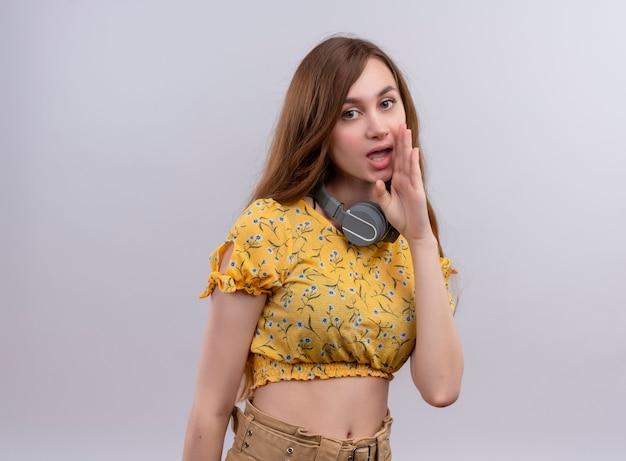 목에 헤드폰을 착용하고 복사 공간이 격리 된 흰 벽에 입 근처에 손을 넣어 속삭이는 어린 소녀