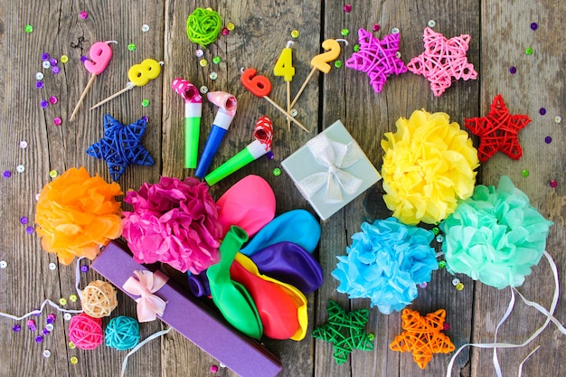Whistles, balloons gifts, candles, decoration on old wooden background