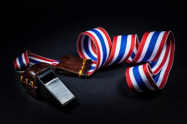 黒の背景にタイの国旗のストラップと笛