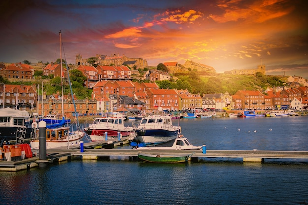 Whitby 수도원은 영국 노스 요크셔에서 일몰 해변 마을과 항구입니다