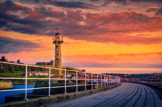 ウィットビー、ノースヨークシャー、イギリスの日没で港の入り口にウィットビー桟橋