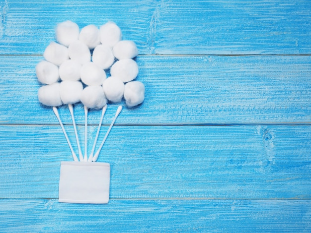 White absorbent cotton balls and cotton buds on wooden blue