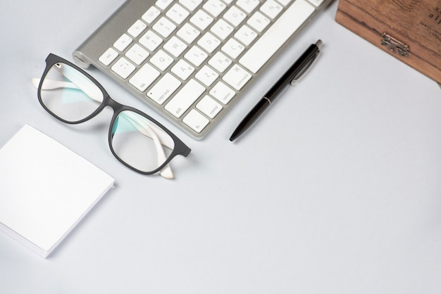 White adhesive note; eyeglasses; keyboard and pen on white background