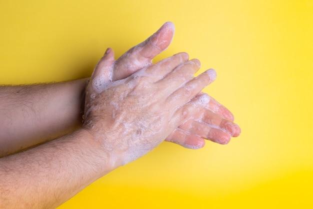 黄色の石鹸で手を洗う白人の成人男性
