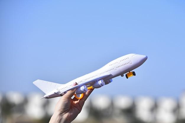 旅行に飛んでいる女性の手の飛行機の夢の白い旅客機のおもちゃモデル
