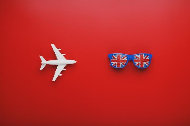 Белый самолет и солнцезащитные очки с флагом соединенного королевства. путешествие в англию.
