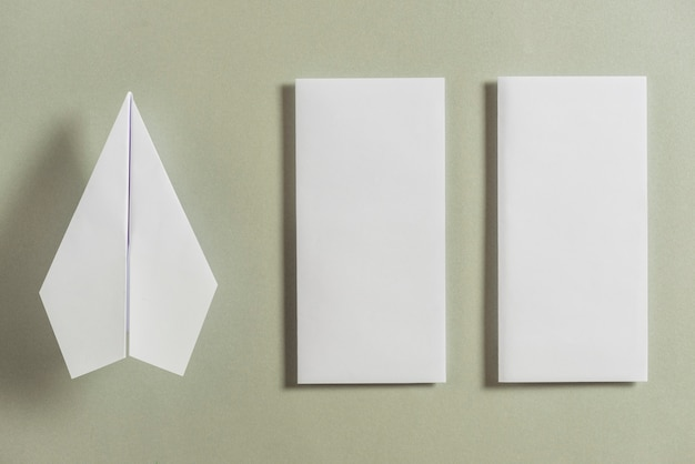 White airplane besides two folded papers on bright background