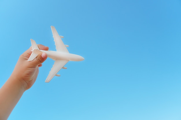 A white airplane in a child's hand against a blue sky.