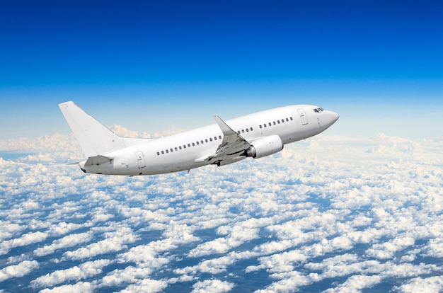 White airplane flies high in the sky above the clouds blue sky.