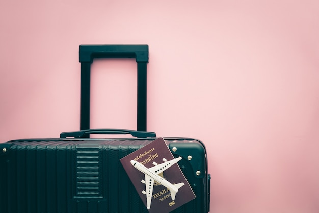 White airplane model, thai passport and black luggage on pink background for travel and journey concept
