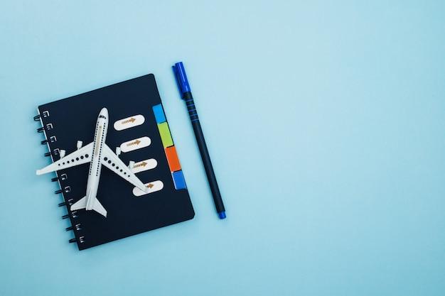 Белая модель самолета с дневником контрольного списка на синем для концепции планирования путешествий