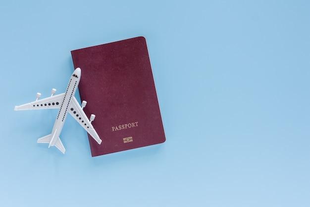 旅行と旅の概念のための青のパスポートを持つ白い飛行機モデル