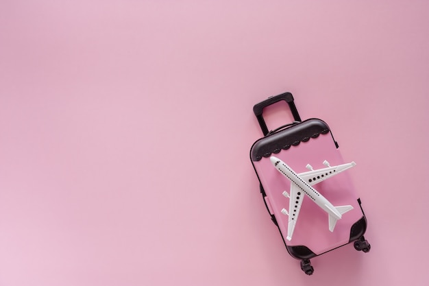 White airplane model with pinky luggage on pink background for travel and journey