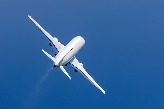 White airplane takes off in the rain in the blue sky.