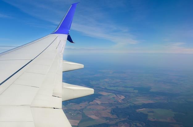 Белое крыло самолета на фоне облаков в небе.