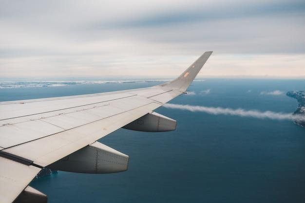 昼間の青い空に白い飛行機の翼