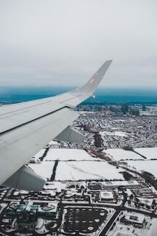 昼間の都市の上の白い飛行機の翼