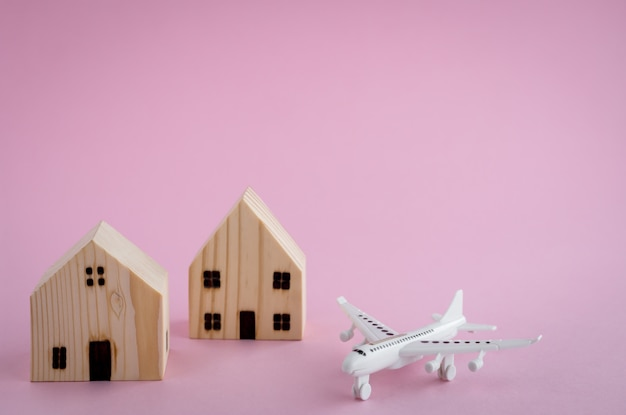 White airplane and wooden house model on pink background for travel concept