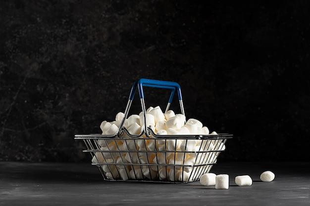 低いキーの暗い背景の食料品バスケットの白い風通しの良いマシュマロ