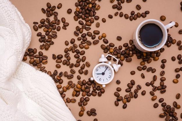 白い目覚まし時計、一杯のブラックコーヒー、居心地の良いセーター、ベージュの背景のコーヒー豆。休憩のために仕事を休んでください。上面図