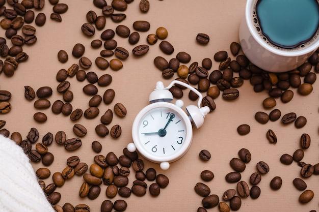白い目覚まし時計、ベージュの背景にブラックコーヒーとコーヒー豆のカップ。仕事を休んでリラックスしてください。上面図