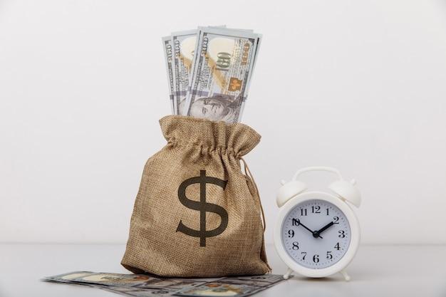 흰색 알람 시계와 달러 돈 가방. 대출, 신용, 모기지 개념.