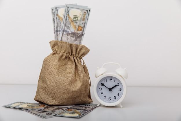 흰색 알람 시계와 돈 가방 대출 신용 모기지 개념